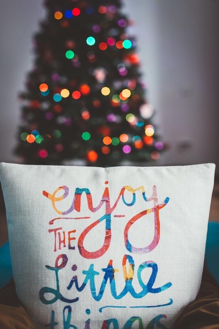 photo cozy décoration de noel avec coussin à lettres inspirantes multicolore et un gros sapin décoré avec guirlande lumineuse