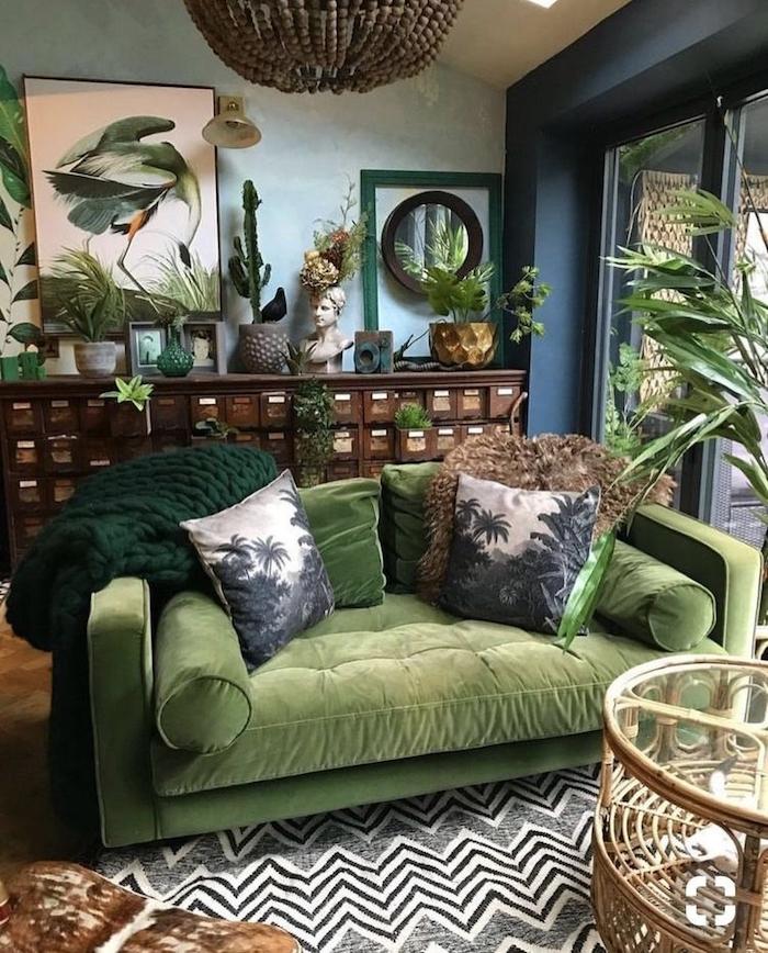 Canapé vert dans un salon avec beaucoup de vertude, murs bleu claire et sombre, peintures originaux, idee deco chambre adulte zen, quelle couleur chambre adulte choisir