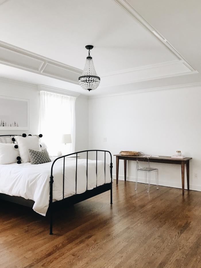 design minimaliste dans une chambre adulte aux murs blancs et plancher en bois foncé avec diy bureau bois brut