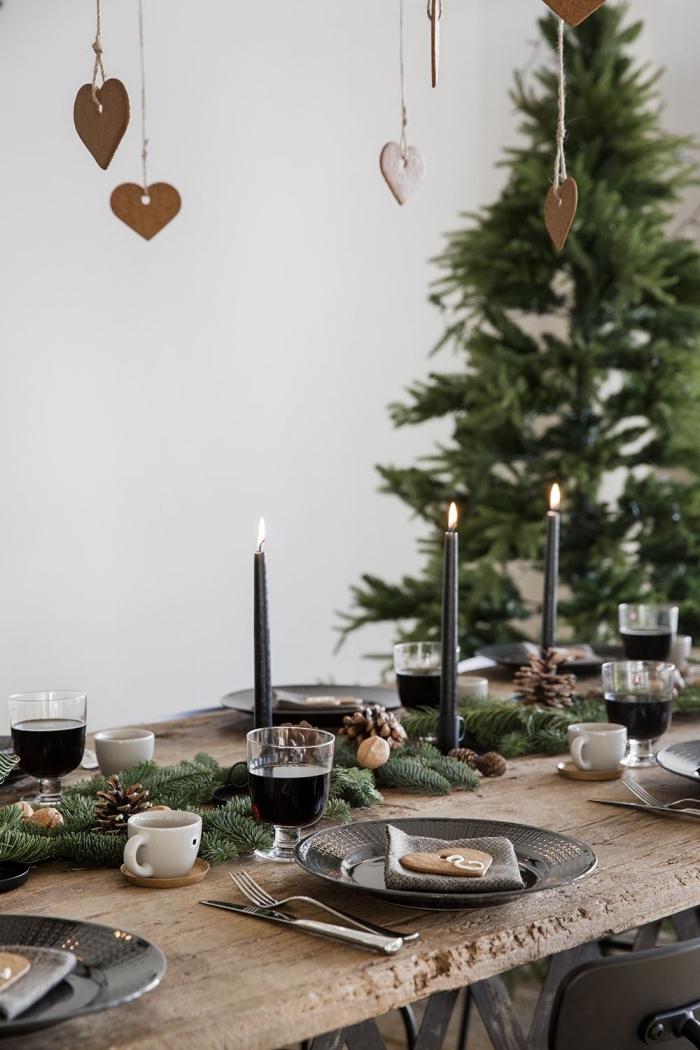 exemple comment décorer une table de style moderne avec objets en bois et noir mat, centre de table noel avec branches de sapin et bougies