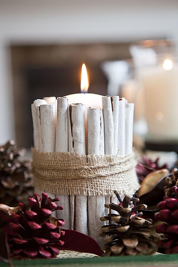 objet de deco de noel a faire soi meme, diy arrangement avec pommes de pin peintes et bougie décoré de bâtonnets cannelle