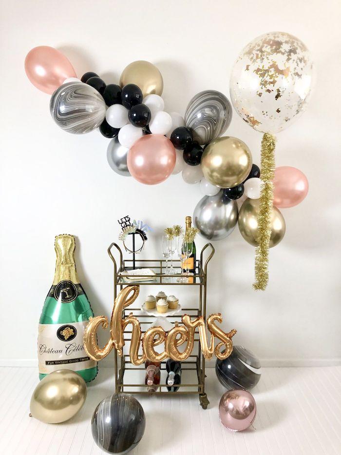 arche de ballons colorés en rose, argent, or, blanc et rose gold, desserte à desserts et bouteille champagne, ballon bouteille champagne