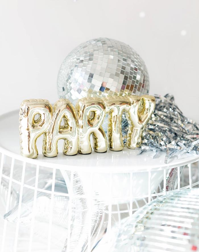 grande boule à facettes argentée et ballons en lettre party sur table blanche, deco blanc et or pour soirée nouvel an