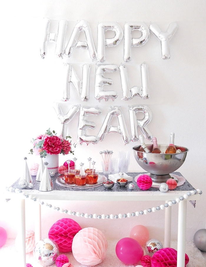 ballon bonne année contre un mur blanc, candy bar de fete avec chapeaux de fete, gourmandises, guirlande de petites boules, deco boules de papier de tailles variées