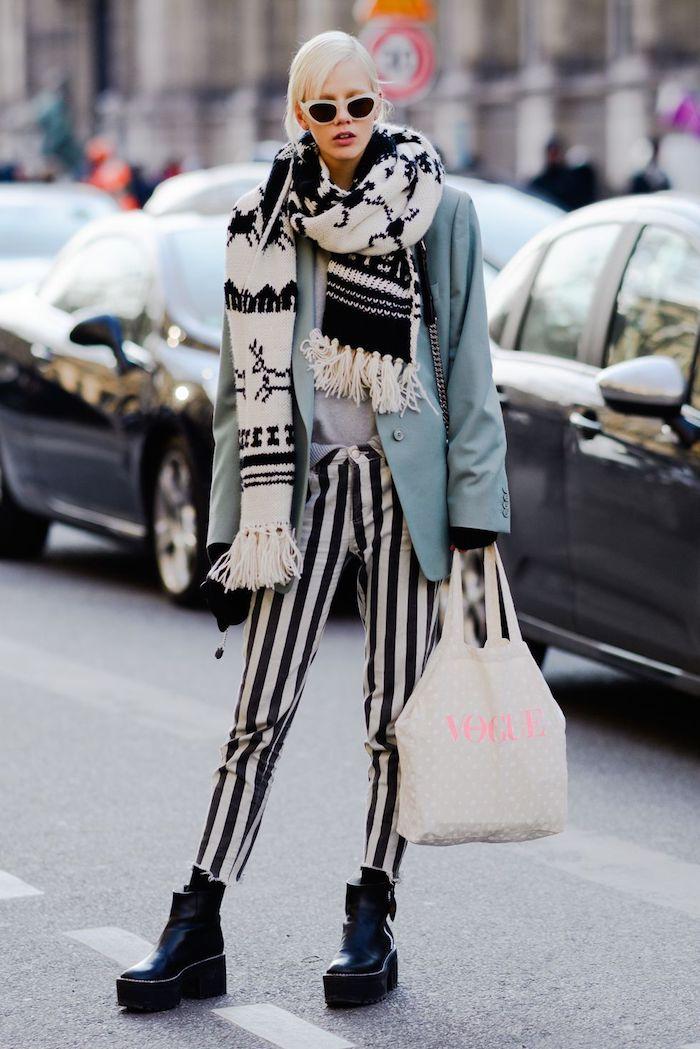 Fille blonde avec lunettes de soleil et grand écharpe hiver, pantalon rayé et veste oversize, ensemble femme style streetwear moderne