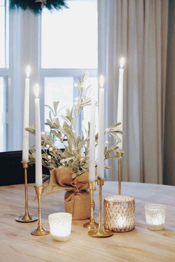 exemple comment décorer une table ronde bois pour Noël avec arrangement stylé en bougeoirs dorés et plante