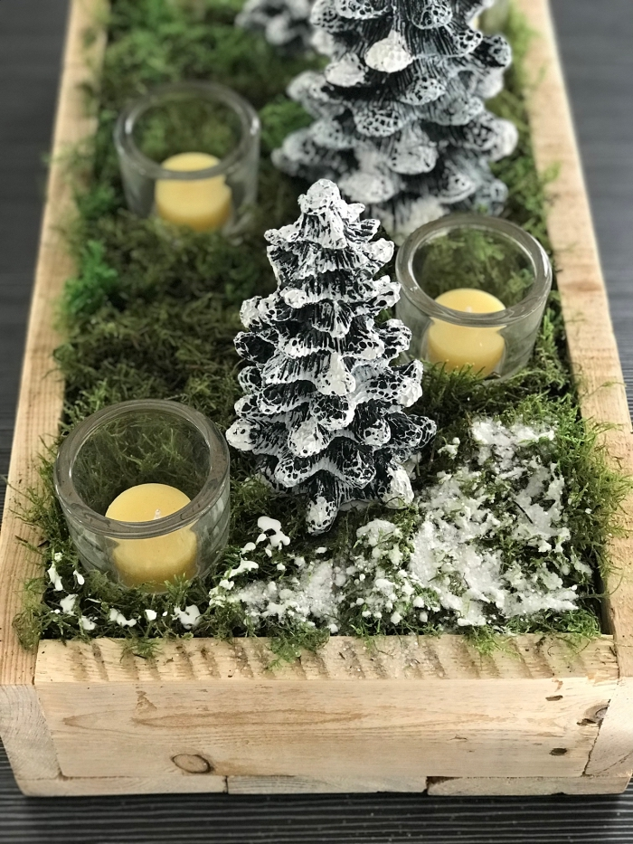 centre de table noel a faire soi meme avec mousse et bougie, diy arrangement de table avec caisse en bois rempli de figurines sapin