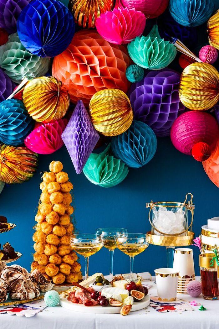 boules de papier colorées sur fond de mur bleu, table candy bar avec plateaux à charcuterie, pièce montée nouvel an, champagne