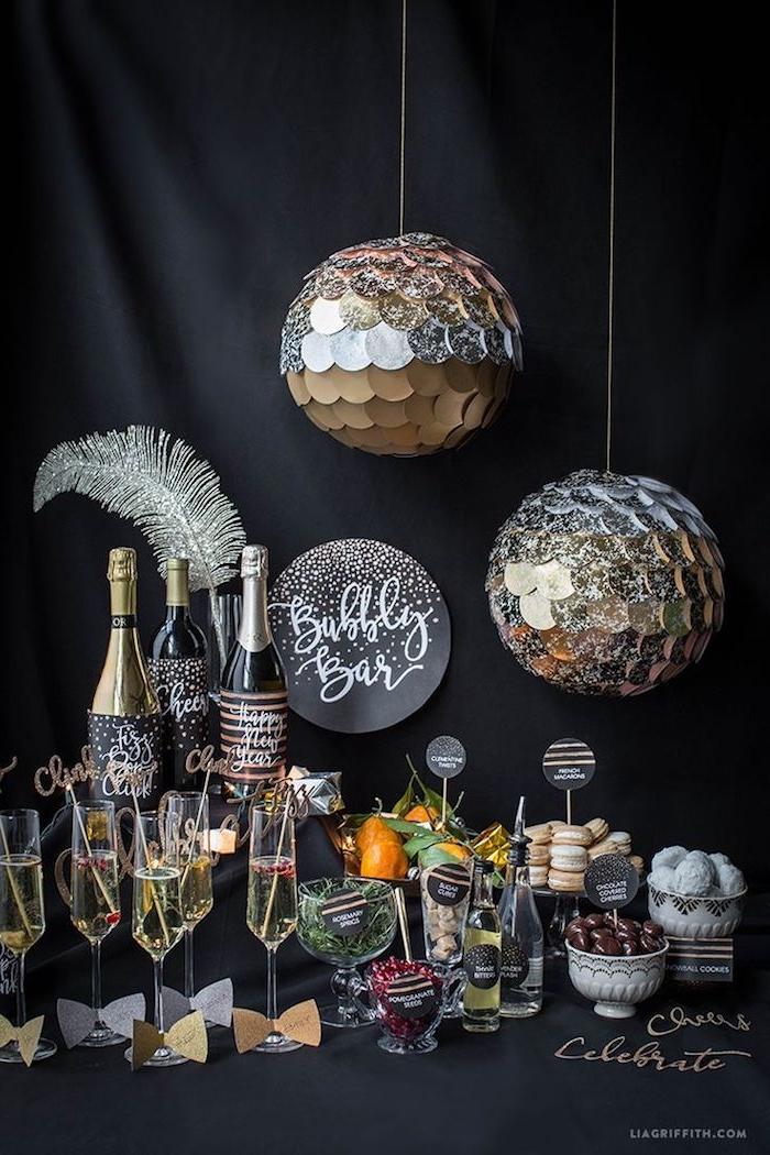 candy bar nouvel an avec boissons et petits apéritifs de nouvel an avec deco boules à facettes argent, plume argentée