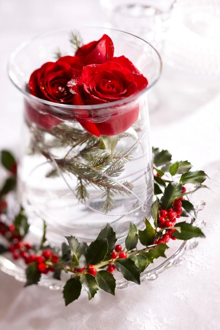 décoration de noel à fabriquer gratuit, bouquet de roses rouges et branches de sapin dans un vase en verre décoré de branches de canneberges