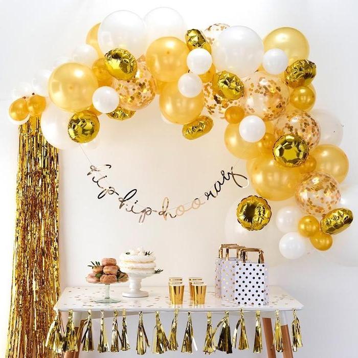 arche de ballons en or et blanc sur mur fond blanc, deco guirlande de pompons à franges dorées, candy bar de fete avec beignets et gateaux