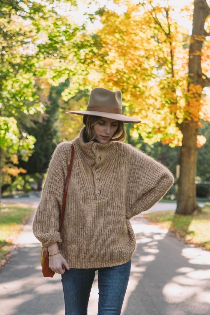 modèle de pull en laine avec boutons et manches larges de couleur beige combiné avec jeans foncés et capeline beige