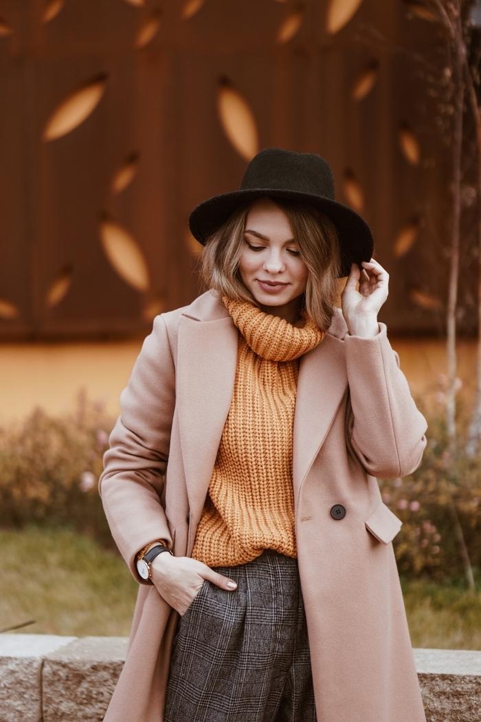 Femme bien habillée, pull orange col roulé, capeline noire, pantalon carotte style, coupe au carré court, tendance coiffure 2020 style feminin moderne