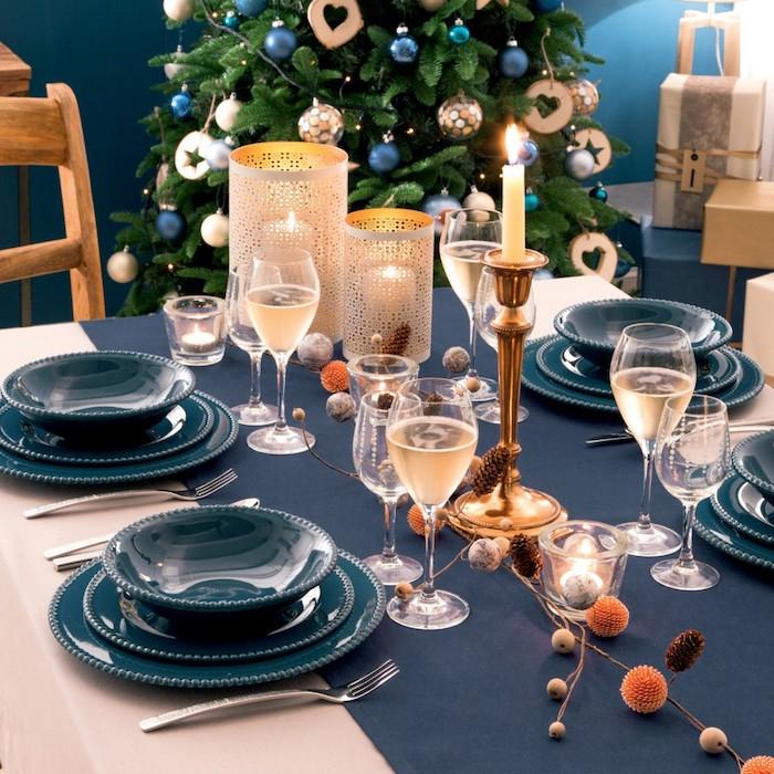 deco elegante de soirée nouvel an avec chemin de table bleu et assiettes bleues, chandelle en or, centre de table floral, bougeoirs originaux