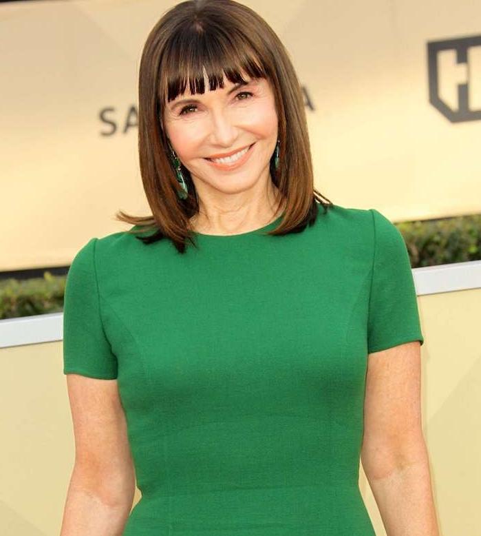 frange droite sur le front et coupe carré mi long cheveux chatain, femme agée en robe verte