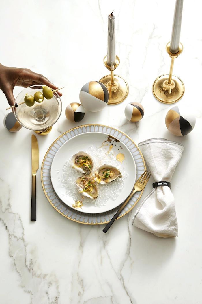 comemnt faire une deco table nouvel an avec chandelles en or, asssiettes en blanc et or, boules decoratives en or, noir, gris et blanc
