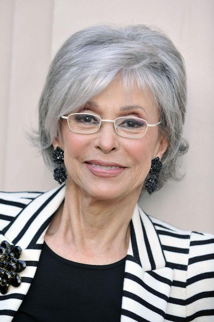 coupe de cheveux court femme 60 ans avec lunettes et frange asymetrique et volume sur le dessus de la tete, cheveux gris poivre et sel