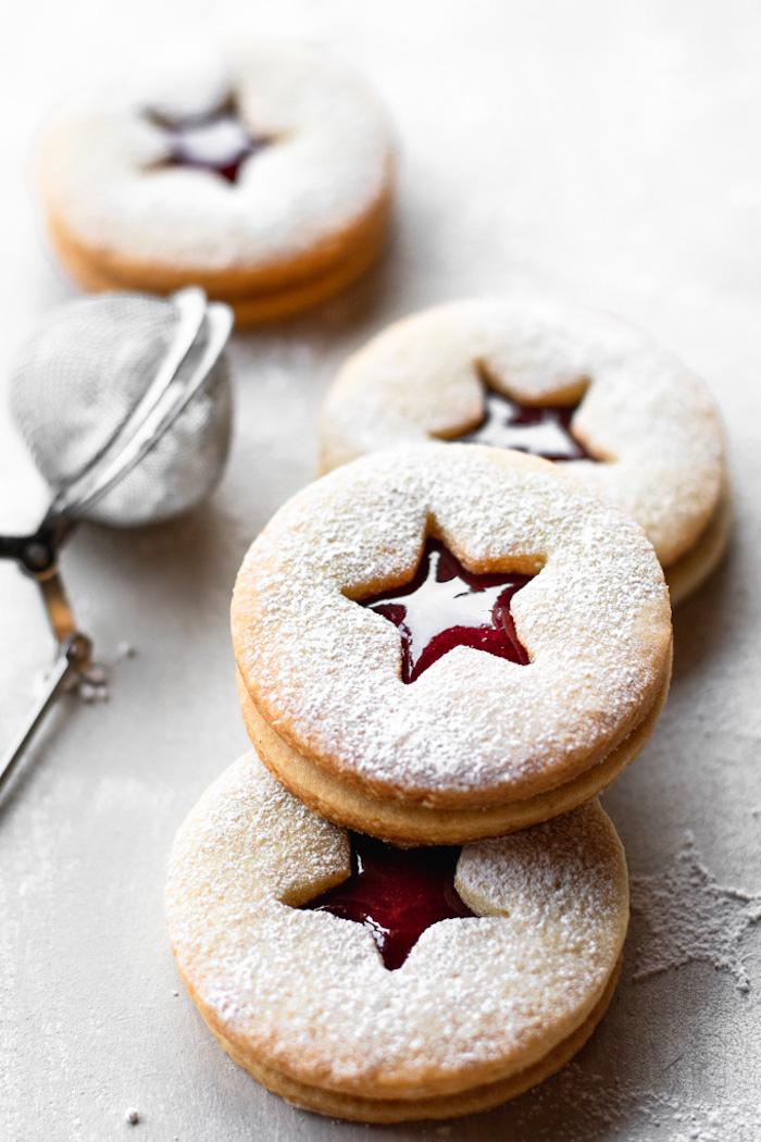 recette biscuit sablé façon linzer avec confiture de fraise, petits gateaux de noel au sucre glace comme decoration