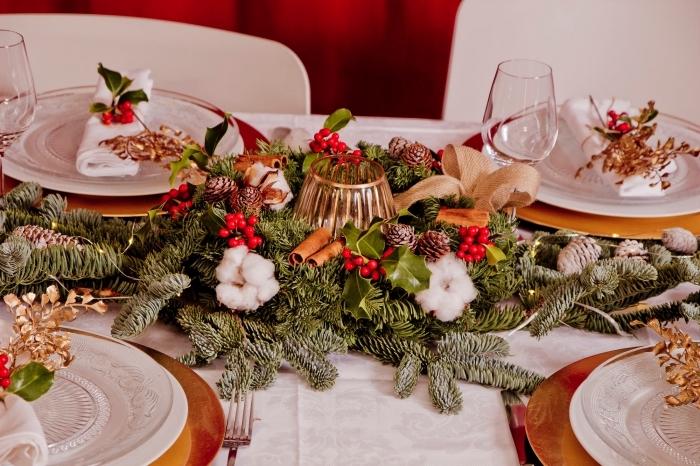 exemple comment décorer une table de Noël avec composition diy, arrangement en branches de sapin décorées de ruban doré