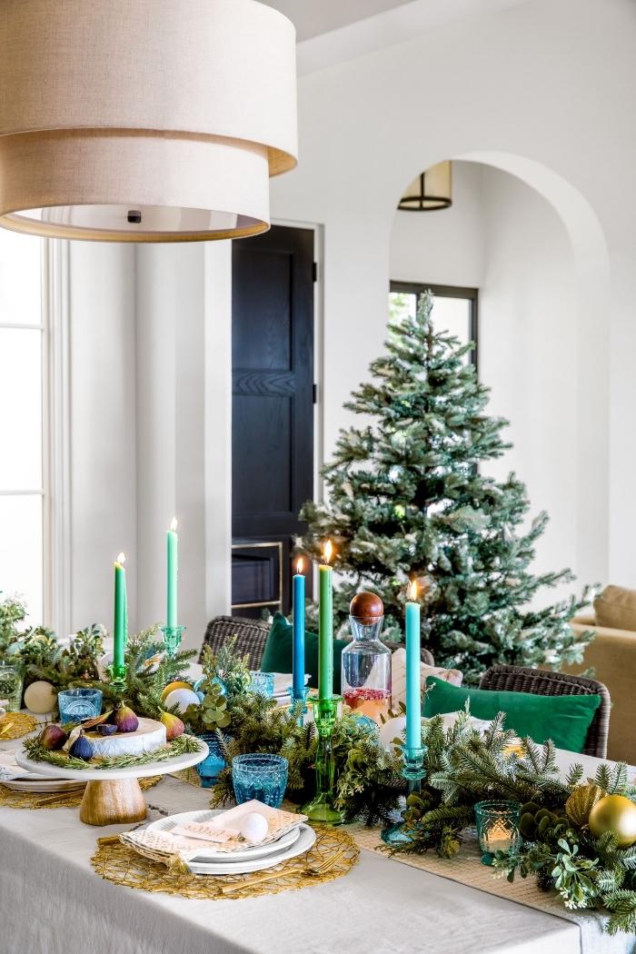 exemple de deco de table de noel chic avec arrangement en branches de sapin et bougies de couleurs vert et bleu