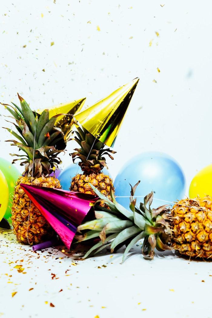 decp ananas pour le jour de l an avec des ananas, ballons colorés et chapeaux de fete entourées de pluie de confettis