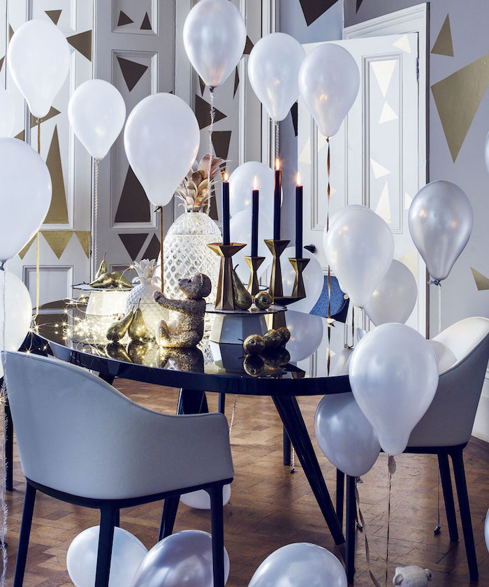 table noire, chandelles or avec bougies noires, guirlande lumineuse et ananas deco, ballons blancs et murs décorés de triangles dorés, theme nouvel an elegant