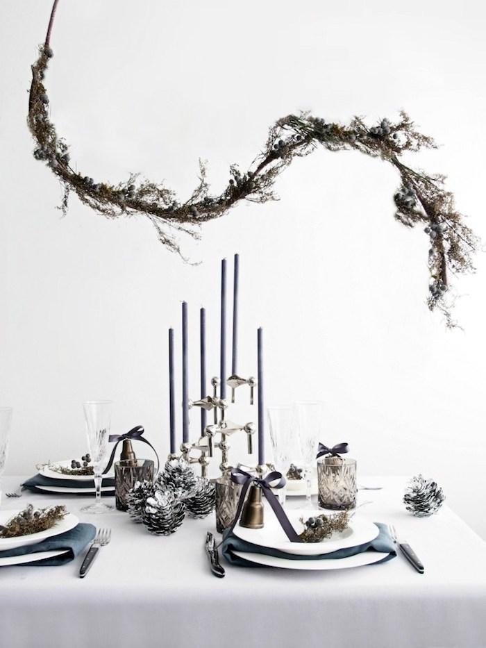 decoration scandinave de nouvel an, branche decorative au dessus d une table à nappe blanche, bougeoir et pommes de pin argentées, motifs deco vegetation