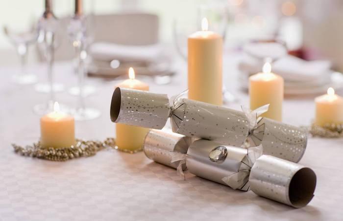 canons à confettis et guirlande de perles autour de bougies de taille variées sur nappe gris et blanc