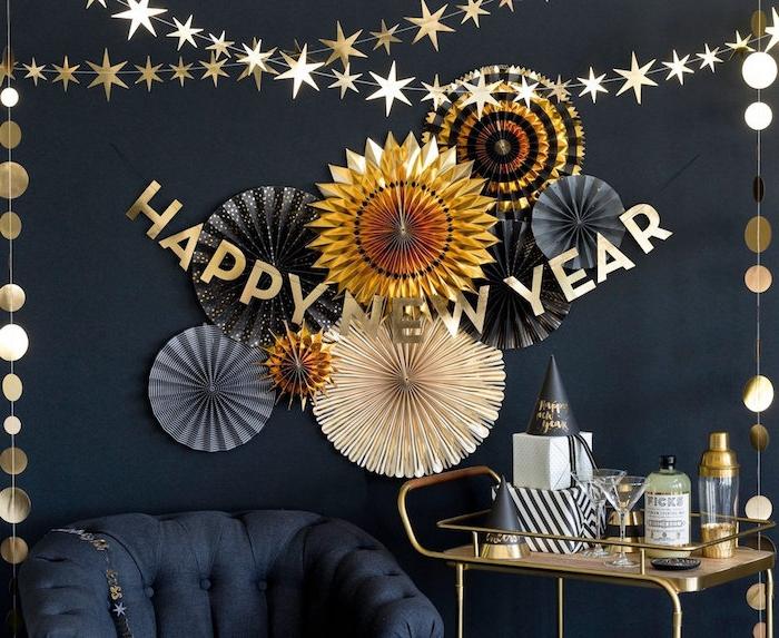 éventails en papier en or et noir et des guirlandes d étoiles dorées, desserte bar avec chapeaux de fete, mur de fond noir