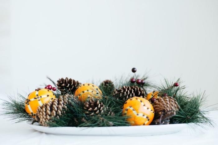 idée décoration de noel à fabriquer gratuit, arrangement de table avec branches de sapin et pommes de pin