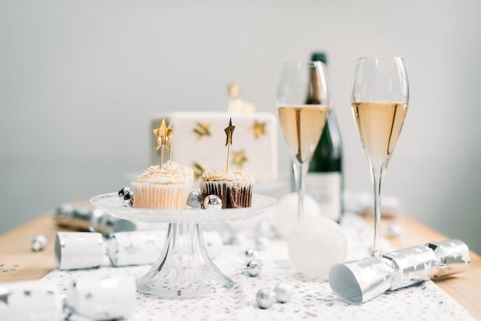 canons à confetis, chemin de table blanc à étoiles argentées, cupcakes sur plateau de service, verres de champagne