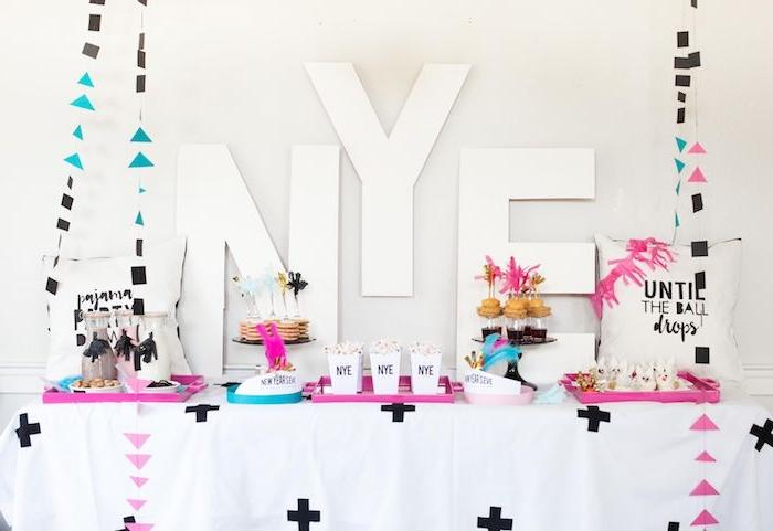 lettres nouvel an sur le fond, table avec plateaux de servie rose et bleu, guirlandes figures geometriques, mini pancakes candy bar de nouvel an