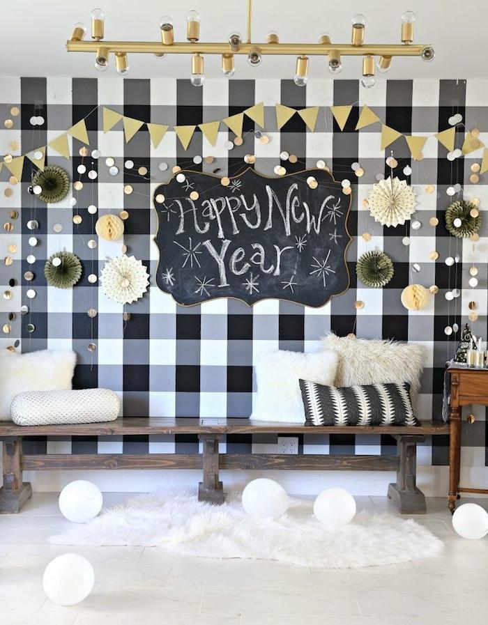 banc de bois décoré de coussins cocooning, mur de fond en noir et blanc, deco eventails et plaque tableau noir ardoise avec bonne anné écrit dessus
