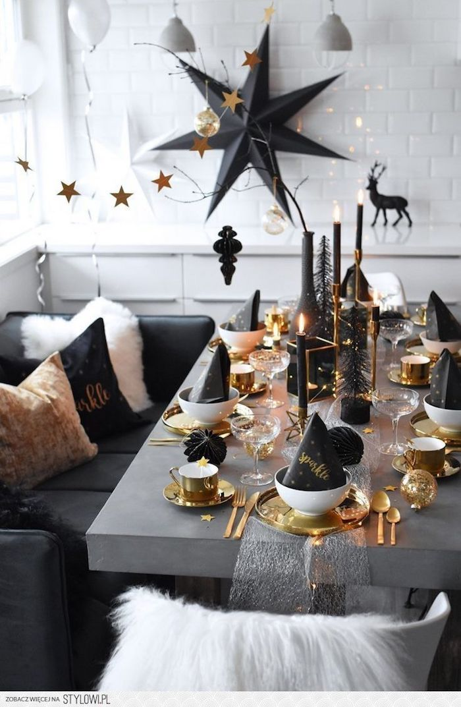 table grise avec couverts et assiettes or et blanc, bougies et accents deco noiors,, deco murale grande étoile noire, deco nouvel an stylée