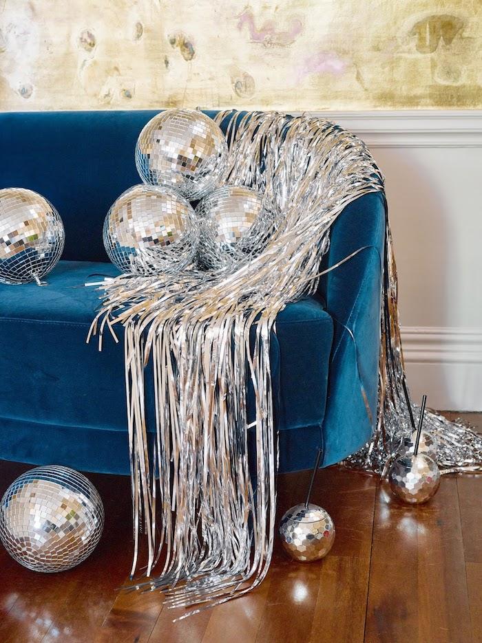 guirland argenté et des boules à facettes sur canapé bleu canard dans un salon cocooning décoré pour le jour de l an