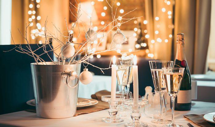 deco de noel a faire soi meme, branche décorées de boules de noel dans seau, bougeoirs en verre avec bougies blanches, guirlande lumineuse sur le fond