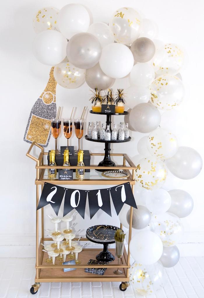 arche de ballons blanc et or autour d une desserte couleur or à accents déco originaux, verres, bouteiles de champagne