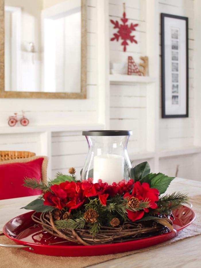 DIY couronne de Noël en branches séchées et pommes de pin décorée avec fleurs rouges, idée de deco table noel DIY