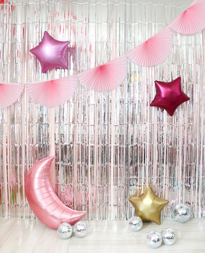 rideau à franges argentées pour décorer un mur avec guirlande d éventails rose, ballons en forme de lune et étoile, balles à facettes