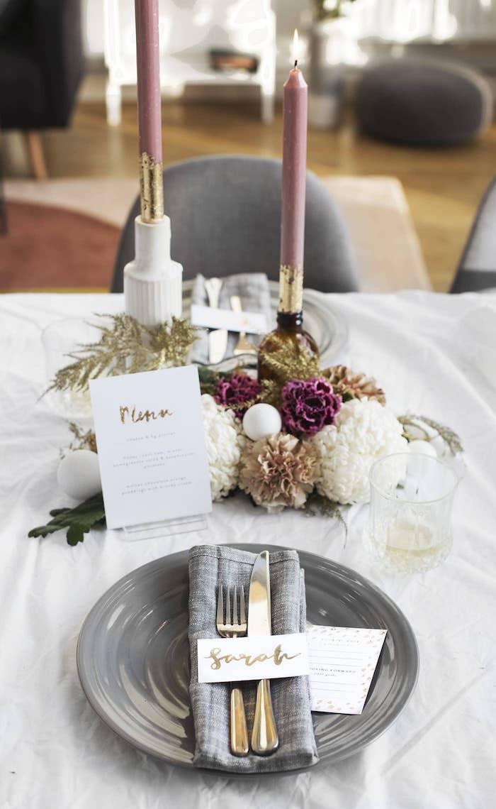 exemple deco table nouvel an avec assiette et serviette grise, centre de table bougies et bouquet de fleurs