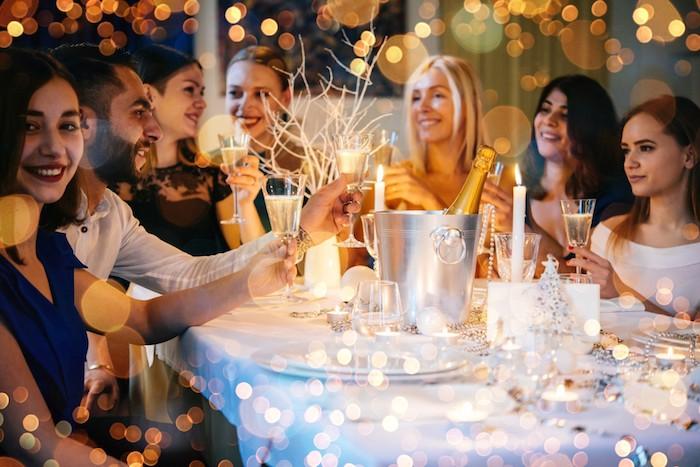 idee jour de l an soirée entre amis autour d une table décorée pour le jour de l an, champagne, nappe et assiettes blanches, figurine sapin de noel, deco guirlande de perles argentées