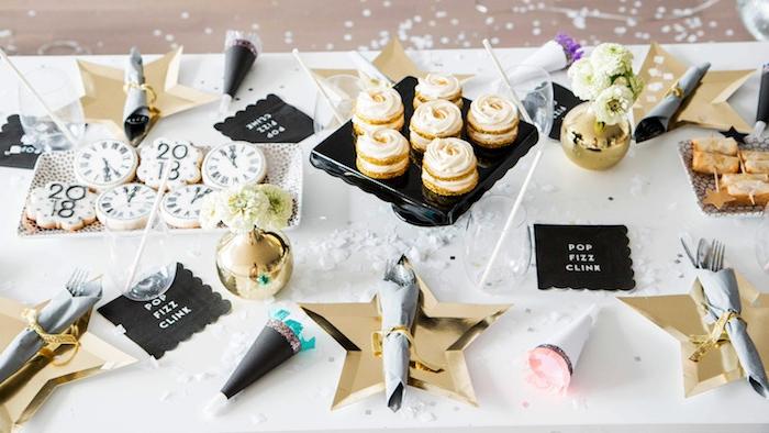 idee deco table nouvel an avec assiettes en forme d étoile en couleur or, canons à confettis de papier, sablés de nouvel an motif horlofe