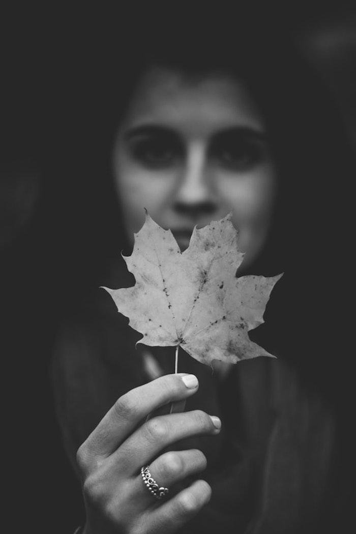 Photo fille portrait, main qui tient feuille d'automne, photo art graphique, photos stylées noirs et blancs aesthetic