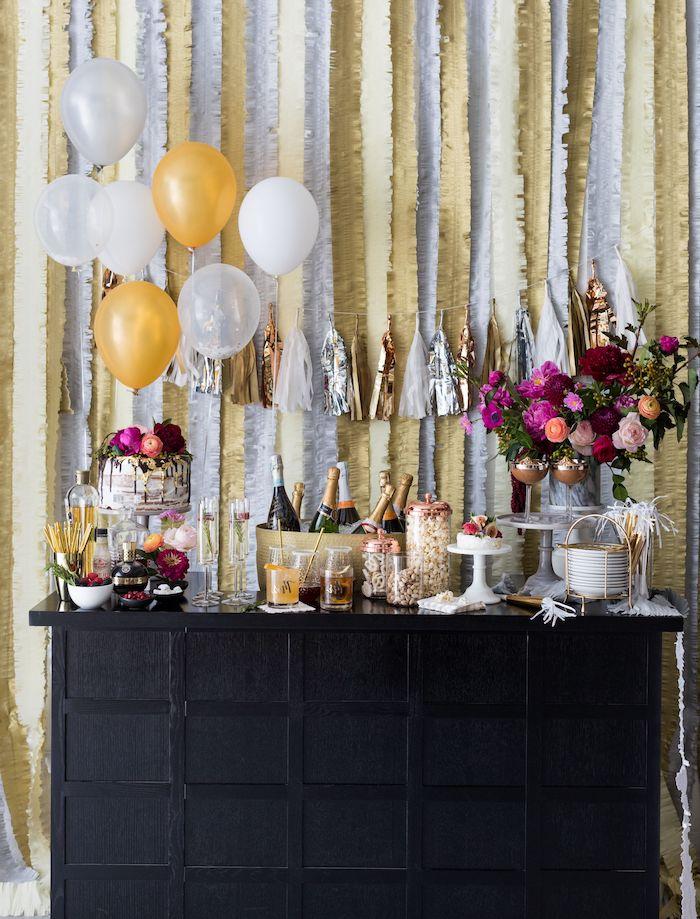 candy bar nouvel an avec verres, bouteilles de champagne, bouquet de fleurs et gateau de nouvel an, devo ballon et guirlandes sur le fond