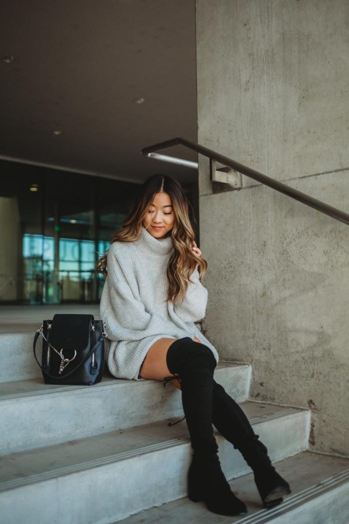 tenue chic d'hiver en pull long femme à col roulé combiné avec bottes longueur genoux noires et sac à dos noir