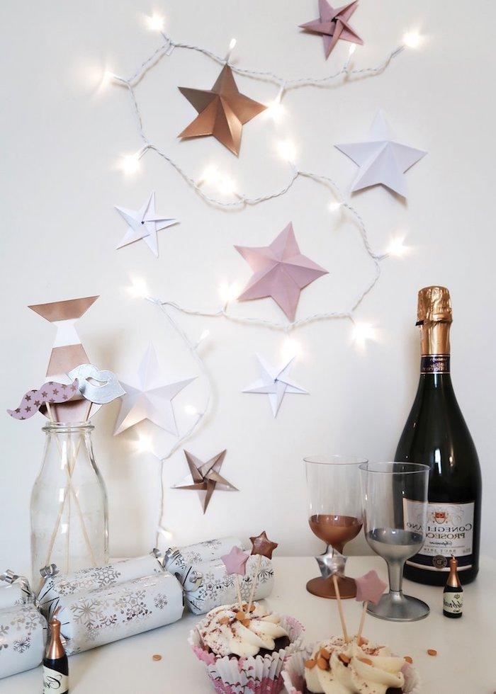 guirlande lumineuse blanche décorée d étoiles de papier, canons à confettis dçoratifs, cupcakes originaux