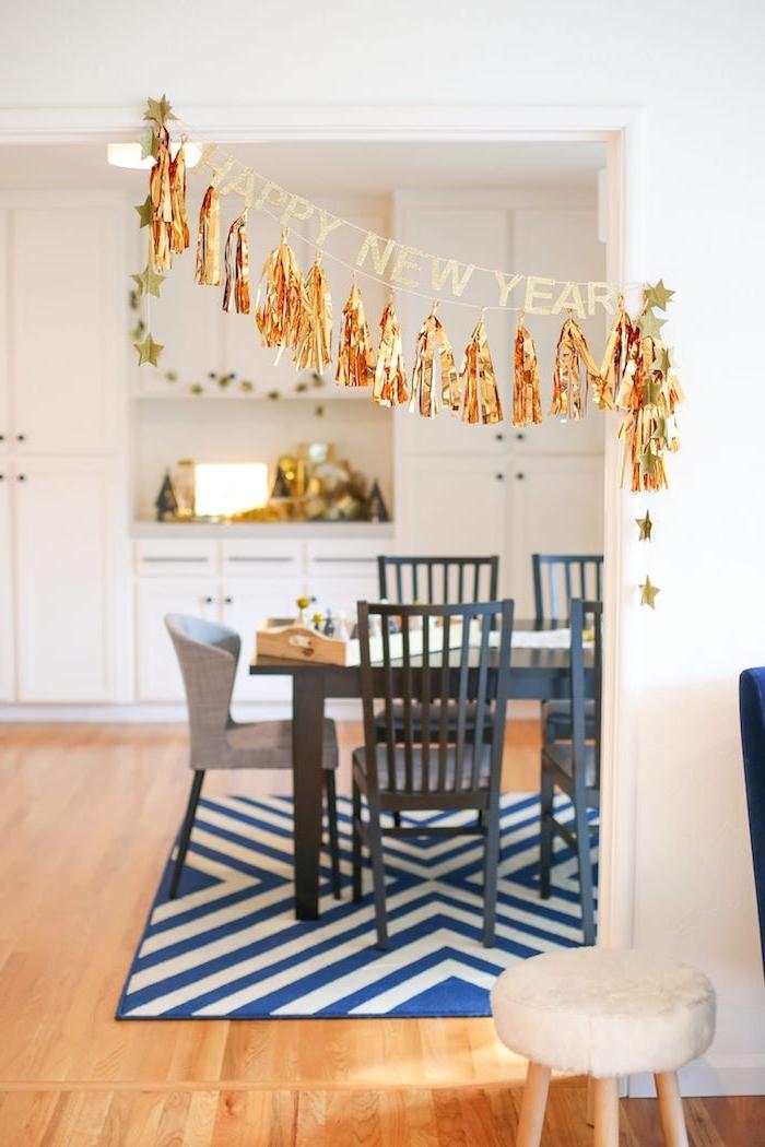 déco salle à manger pour le jour de l an en guirlande de pompons à franges dorées et message bonne année