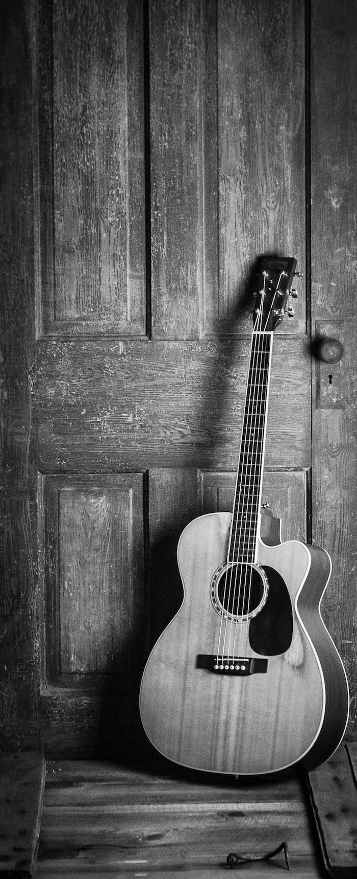Guitare sur une porte d'entrée en bois, fond sombre, photo monochrome élégante à utiliser sur son portable