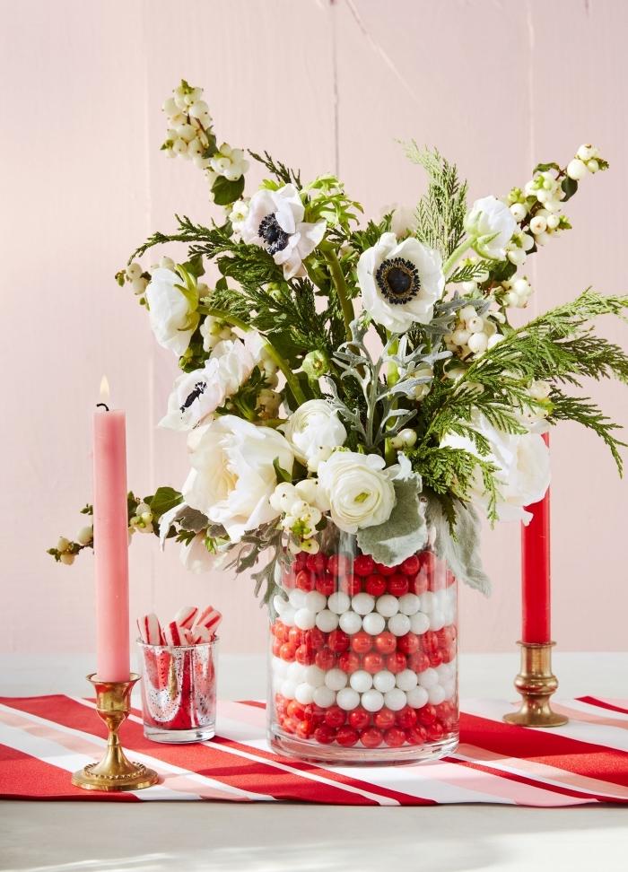 centre de table noel facile avec fleur, diy composition florale en blanc et vert dans un contenant en verre rempli de boules rouges et blanches