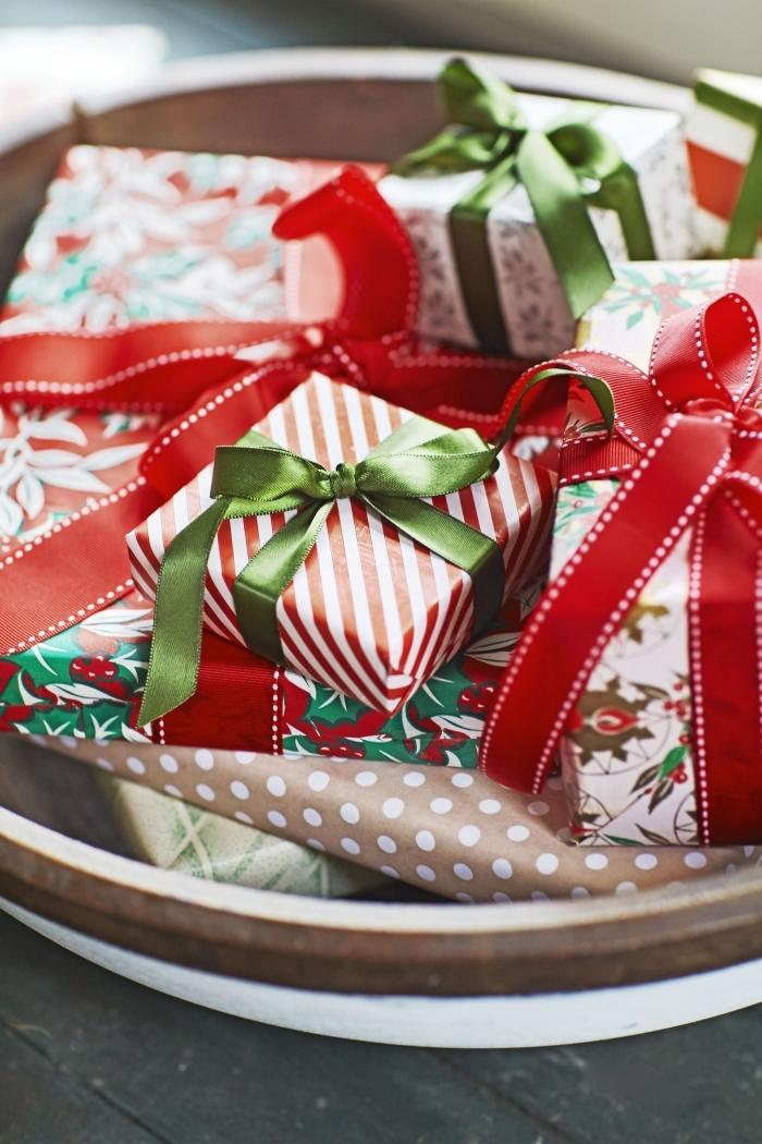 décorer la table de Noël avec objets fait main, centre de table dans une assiette bois remplie de cadeaux emballés diy